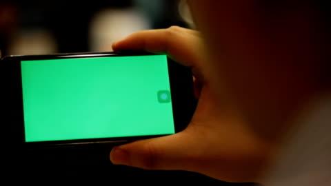 sulla spalla girato di utilizzando smartphone con schermo verde - composizione orizzontale video stock e b–roll