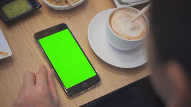 vídeos de stock, filmes e b-roll de por causa de dose de ombro de usar o smartphone no restaurante, tela verde - mesa