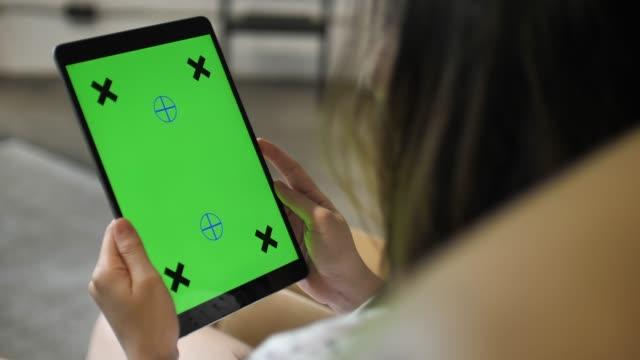 디지털 태블릿을 사용 하 여 여자의 어깨 샷, 녹색 화면 - 태블릿 스톡 비디오 및 b-롤 화면