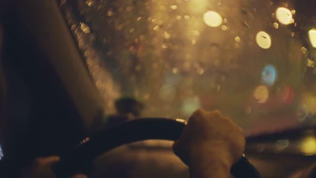 över skuldra skott av kvinnor som kör en bil i regnet på natten - vindruta bildbanksvideor och videomaterial från bakom kulisserna