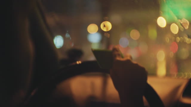 Over shoulder shot of women driving a car in the rain at night