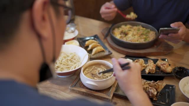 Over Shoulder Shot - Two Men eating in Japanese restaurant while have face mask on, New normal