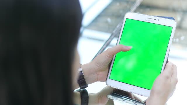över axeln sköt kvinna använder surfplatta grön skärm - telefonmeddelande bildbanksvideor och videomaterial från bakom kulisserna