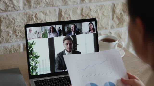 over shoulder view of businesswoman video conference calling colleagues team - дистанционный стоковые видео и кадры b-roll