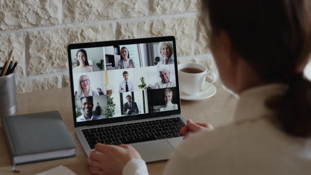 vídeos de stock e filmes b-roll de over shoulder view of businesswoman video conferencing diverse business team - isolado