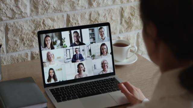 vídeos de stock e filmes b-roll de over shoulder view of employee communicating with team by webcam - video call