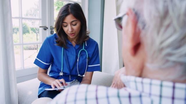 年配の男性、家庭訪問の看護師の肩のビューの上 ビデオ