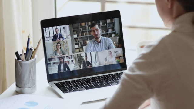 Over shoulder view of remote worker participating group virtual meeting