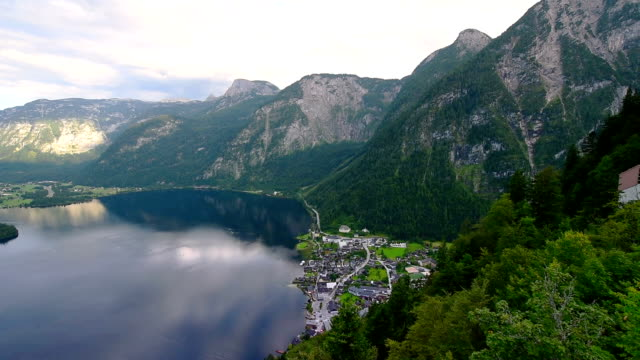 over the historical town of hallstatt with its beautiful churches. famous touristic hot spot in the middle of the austrian alps - styria filmów i materiałów b-roll