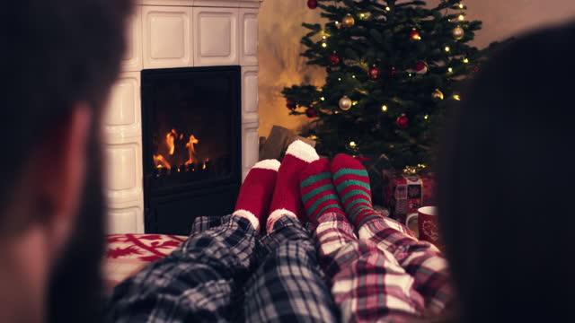 över axeln par fötter i mysiga jul ull strumpor nära öppen spis med dekorerad xmas träd och tee cup i bakgrunden - strumpa bildbanksvideor och videomaterial från bakom kulisserna
