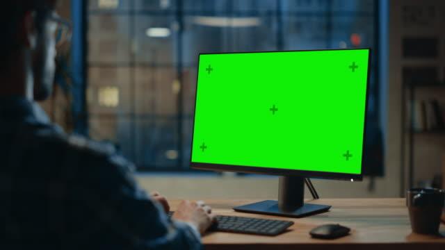 어깨 너머: 모형 녹색 화면이있는 데스크톱 컴퓨터를 사용하여 책상에 앉아있는 창조적 인 청년. 시티 윈도우 뷰가 있는 세련된 오피스 스튜디오에서의 저녁 - 책상 스톡 비디오 및 b-롤 화면