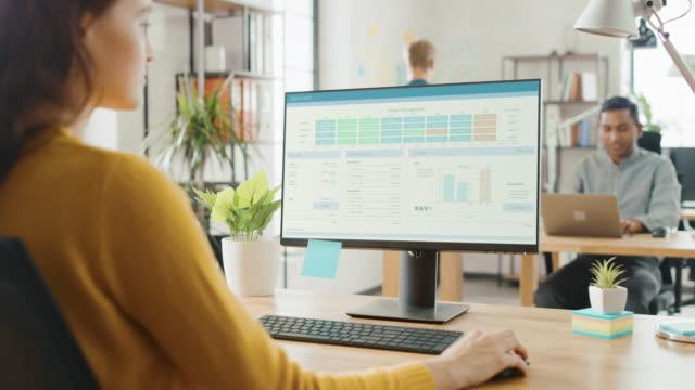 omuz over: yaratıcı genç kadın masası, proje yönetimi, istatistik ve grafikler gösteren ekran ile masaüstü bilgisayar kullanarak oturan. çalışma uzmanları çeşitli ekibi ile ofis - masaüstü bilgisayar stok videoları ve detay görüntü çekimi