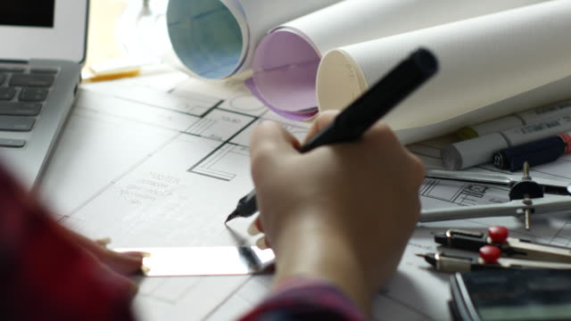 Over the shoulder Female Architect drawing on blueprint video