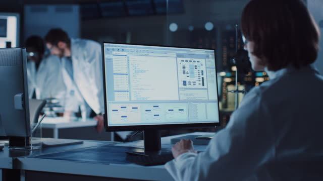 ショルダーショット: 女性 it 科学者は、システムの監視と制御プログラムを示すコンピュータを使用しています。科学者とのバックグラウンド技術開発研究所では、エンジニアが働く - 研究所点の映像素材/bロール