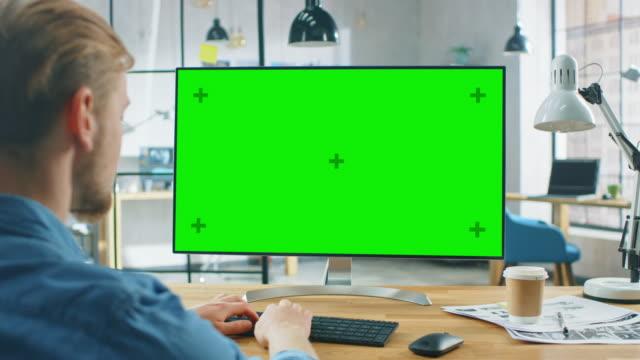 어깨 를 통해 샷 : 남자는 자신의 책상에 앉아있는 동안 녹색 모형 화면과 노트북 컴퓨터를 사용합니다. 배경 세련된 현대 오픈 스페이스 크리에이티브 비즈니스 오피스 - 책상 스톡 비디오 및 b-롤 화면