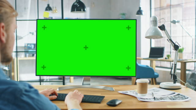 omuz shot over: adam onun masasında otururken yeşil mock-up ekran ile dizüstü bilgisayar kullanır. arka planda şık modern açık alan yaratıcı iş ofisi - masaüstü bilgisayar stok videoları ve detay görüntü çekimi