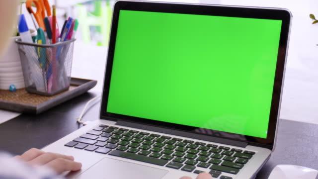 stockvideo's en b-roll-footage met over de schouder geschoten van de aziatische jongen te kijken naar groen scherm. office persoon met behulp van laptop computer met laptop groen scherm, - sjabloon