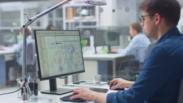 över shoulder shot av ingenjör arbeta med cad-programvara på stationär dator, visar skärm tekniska utkast och ritningar. inom bakgrunds teknik som specialiserar sig på industriell design - man architect computer bildbanksvideor och videomaterial från bakom kulisserna