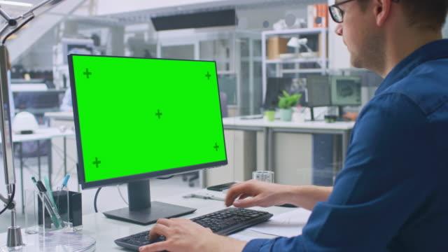 över shoulder shot av ingenjör arbeta med grön mock-up screen stationär dator. i bakgrunds teknik facility med specialister arbetar på ritningar och ritningar med industriell design - man architect computer bildbanksvideor och videomaterial från bakom kulisserna
