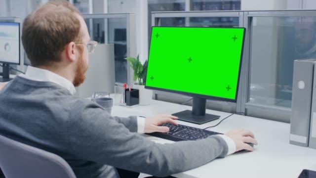 büyük parlak açık uzay ofisi yeşil mock-up ekran masaüstü bilgisayar kullanarak motive ofis işçisi omuz shot over - masaüstü bilgisayar stok videoları ve detay görüntü çekimi