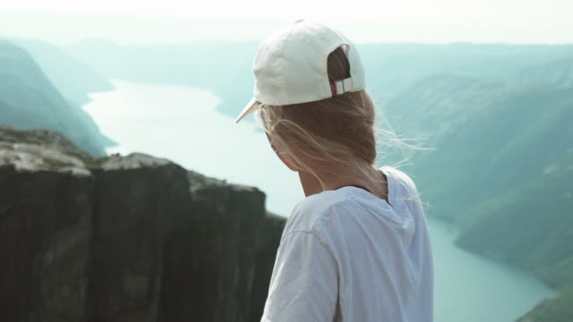 over the shoulder view of preacher pulpit rock and nature in the background - fiordo video stock e b–roll