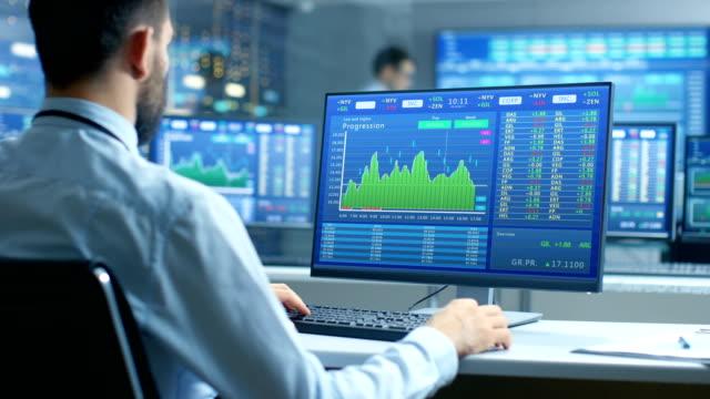 株価表示器数字やグラフを示すコンピューターで作業して株式市場の貿易業者の肩の表示。 ビデオ
