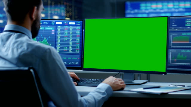 over the shoulder view of stock market trader working on a computer with isolated mock-up green screen and second display showing number ticker with graphs. in the background monitors with relevant information. - stock broker stock videos & royalty-free footage