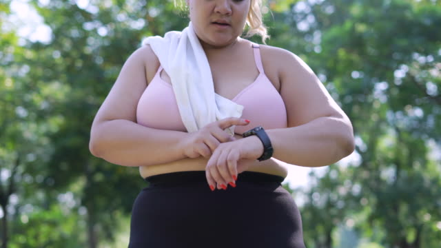 over weight donna correre e impostare smart watch - body positive video stock e b–roll