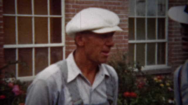 1940: Overalls man talking to fedora hat formal fashion dude. video