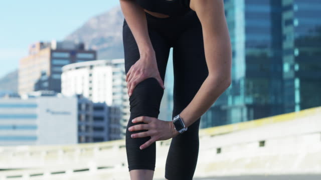 Overexertion on your body can lead to pain 4k video footage of a sporty woman holding her knee while exercising in the city knee stock videos & royalty-free footage