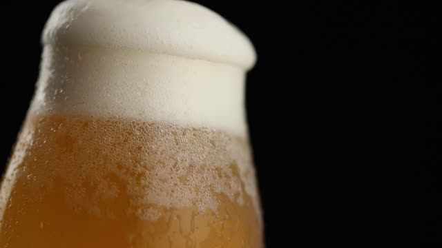 Overflowing beer glass Detail of a cold beer in a glass overflowing, froth leaking down the glass lager stock videos & royalty-free footage