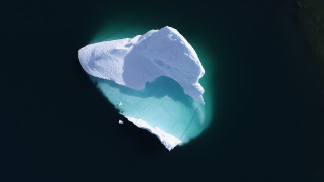 vídeos de stock e filmes b-roll de overhead aerial drone footage of a large iceberg in greenland - lifting up - iceberg