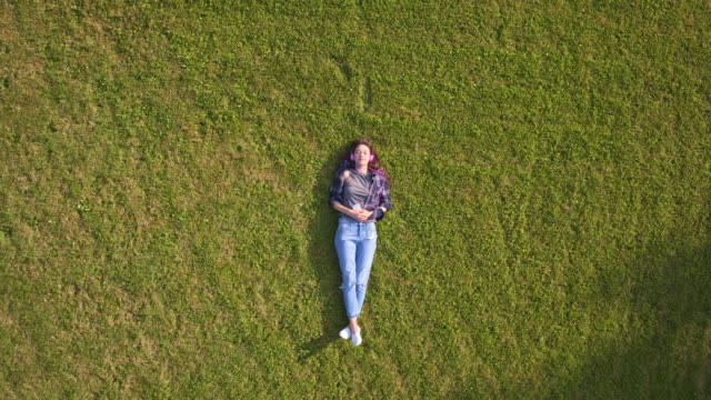 overhead aerial drone footage of woman enjoying music on grass - grass stock videos & royalty-free footage