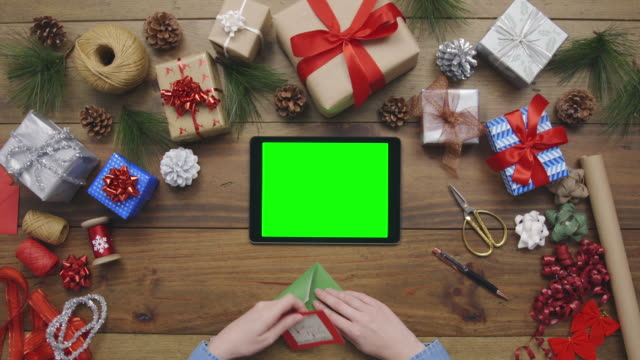 Overhead aerial footage of woman putting Christmas card into envelop Aerial lockdown footage of woman putting greeting card into an envelope at table. Personal perspective of female is with Christmas gifts. Overhead flat lay of digital tablet and craft equipment surrounding lady's hands. branch plant part stock videos & royalty-free footage
