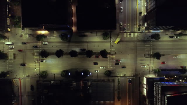 Overhead Aerial of Cars Driving by City Blocks at Night Passing Intersection video
