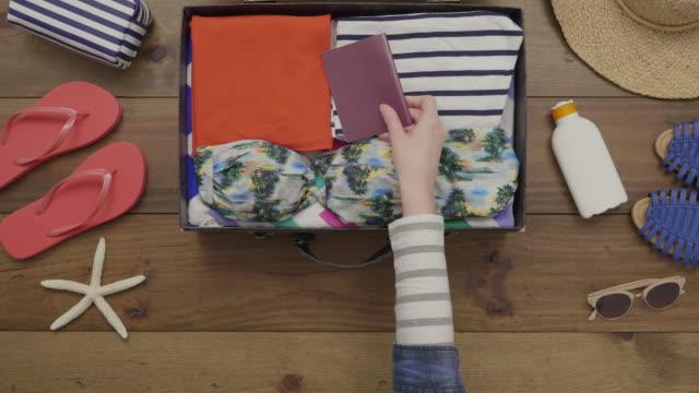 女性服にスーツケースにパスポートを配置するのオーバーヘッドのアンテナ ビデオ