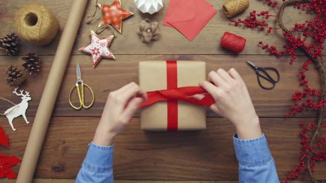 クリスマス プレゼントに赤いリボンを結ぶ女の頭上のアンテナ - クリスマスプレゼント点の映像素材/bロール