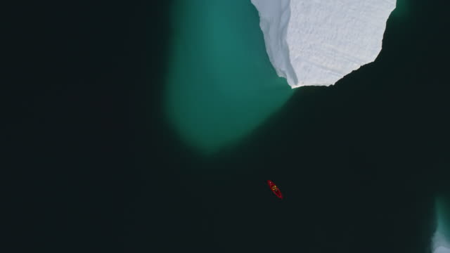 overhead aerial shot of a kayaker kayaking between two icebergs in greenland - fiordi video stock e b–roll
