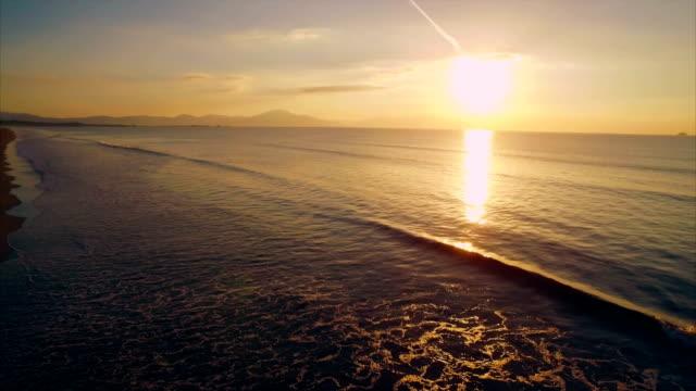 stockvideo's en b-roll-footage met overhead luchtfoto video van vrouw stond op strand tijdens zonsondergang - handen op de heupen