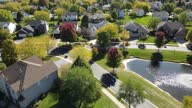 istock Overhead aerial view of colorful autumn trees, residential houses and yards with drainage pond along suburban street in Chicago area. Midwest USA. 4K 1285571673
