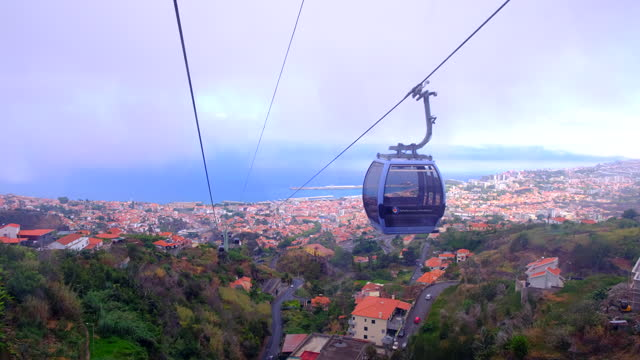 Overhead cable car or Teleférico above the city of Funchal in the clouds on Madeira island in Portugal