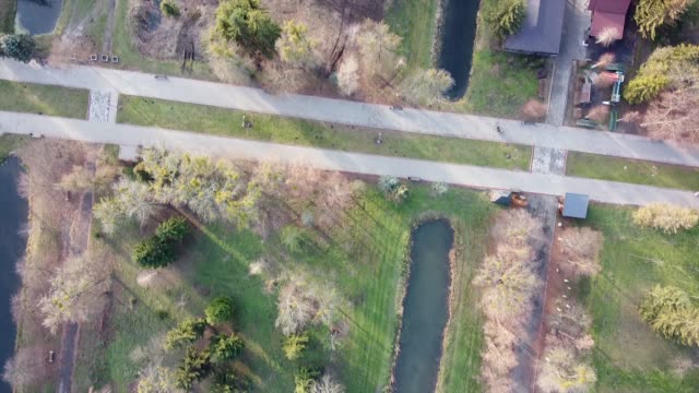 Overhead drone footage of a public park with a canals and landscaped scenery during sunny day.