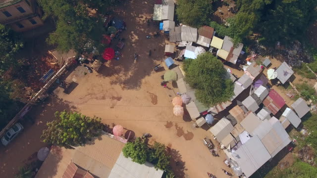 Overhead drone shot of a small market intersection, fresh products for sale in village