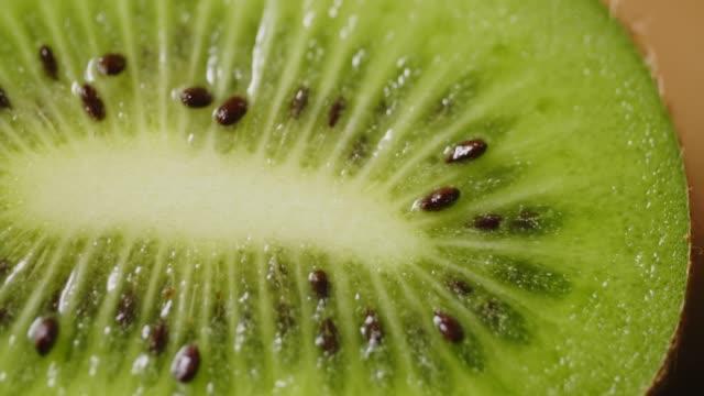 overhead extrem närbild skott av roterande kiwi slice på bord - kiwifrukt bildbanksvideor och videomaterial från bakom kulisserna