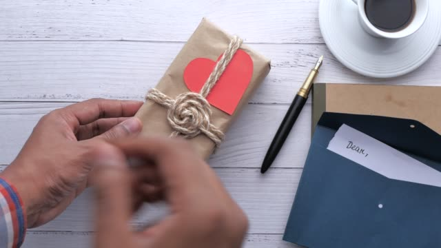 Overhead hand putting gift box on table