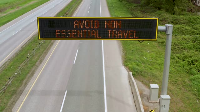 Overhead highway advisory and information sign on the almost empty Highway 1 says Avoid Non Essential Travel