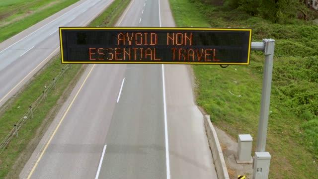overhead-autobahn-beratungs- und informationsschild auf dem fast leeren highway 1 sagt avoid non essential travel - schild stock-videos und b-roll-filmmaterial