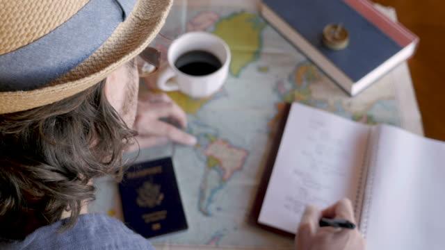 overhead of man planning a trip of a lifetime and writing in journal - fare una prenotazione video stock e b–roll