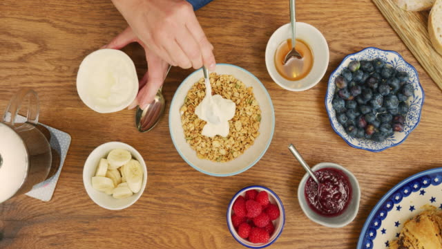 Overhead Of Woman Adding Healthy Ingredients Over Granola