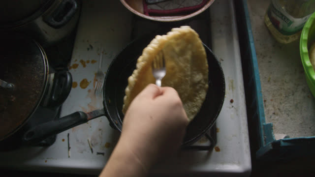 Overhead Shot of a Native American Woman's Hand Using a Fork to Remove a Tortilla (Fry Bread) from a Pan with Oil on a Stovetop